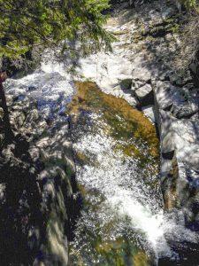 l'acqua che scorre sulla roccia liscia della cascata di sopra illuminata dal sole